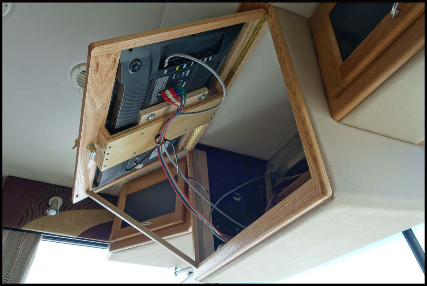 Front overhead TV RV cabinet lifted to show wiring